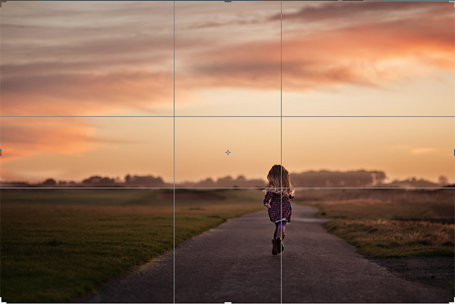 Little girl in a checked dress running into the sunset.