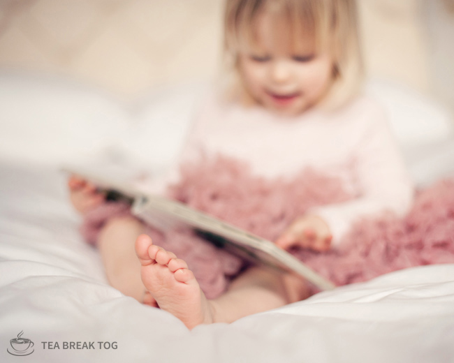 Image of a little girls toes. The girl is wearing a pink tutu and reading a book.