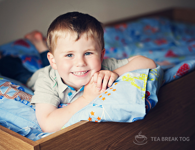 Little boy posing on his bunkbed in his bedroom.