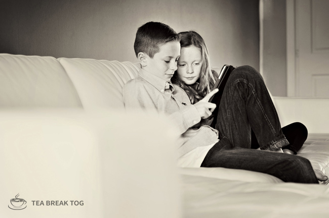 Black and white image og a young boy and girl sitting on a white sofa playing on a tablet